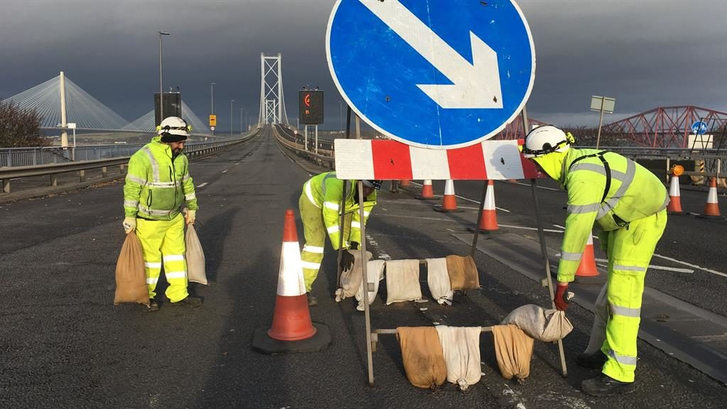 Heavy weather: Workers on the Forth Bridge put sandbags on a sign to weigh it down ahead of the storm PICTURE: PA
