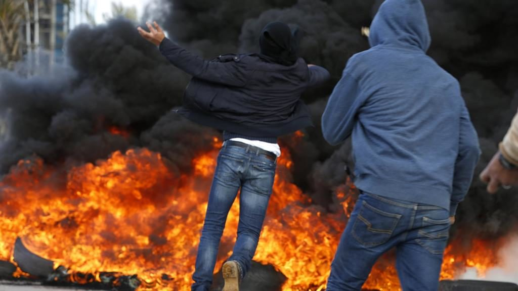 Stoked up: Palestinian protesters set fire to a tyre wall near an Israeli checkpoint in Ramallah PICTURE: GETTY