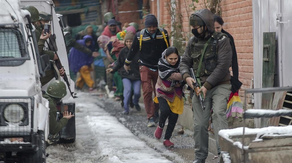 Safe passage: Soldiers lead families out of the area where gunmen opened fire PICTURE: AP