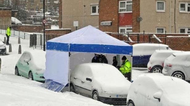 Tragic: Police at the spot where a woman, 75, was found dead beside a parked car in Leeds