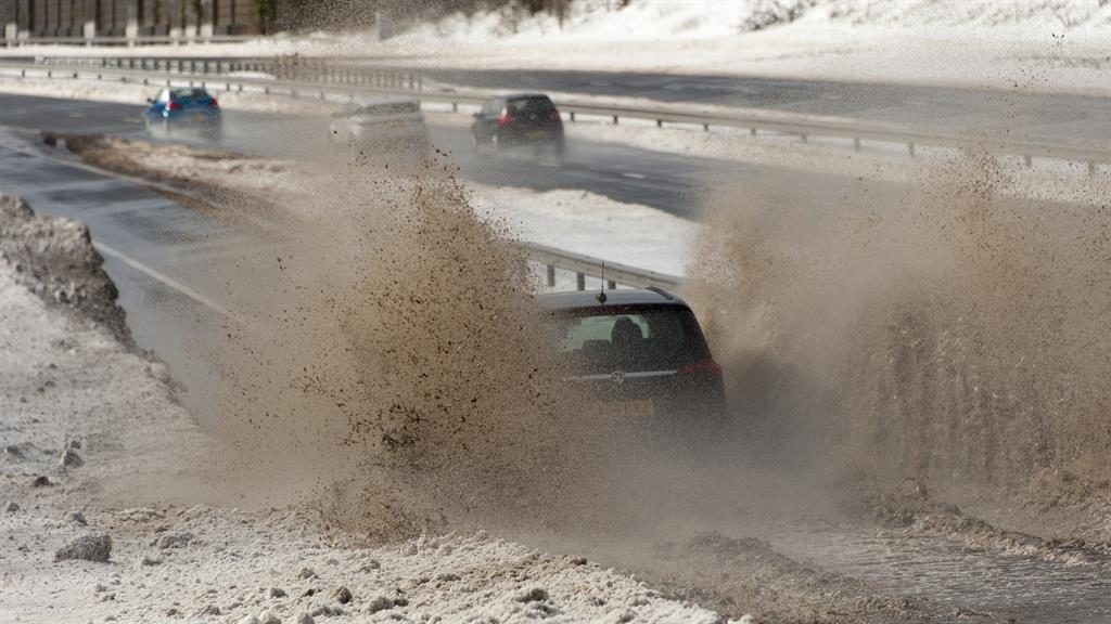 Flood-wheel drive: Cars make their way through melting snow on the A465 in South Wales PIC: LNP
