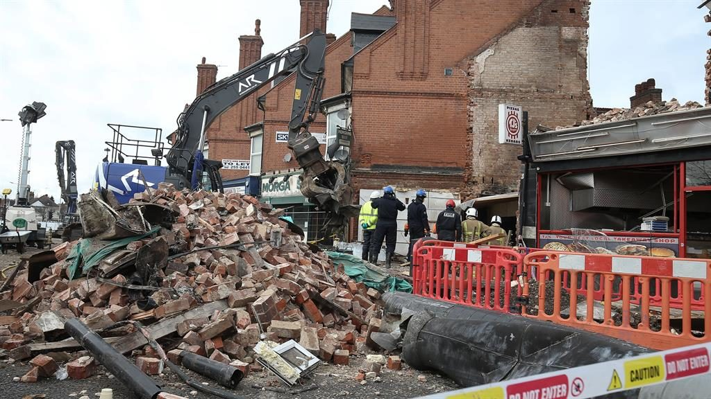 Rubble: Emergency crews at the scene after the blast ripped apart shop and flat, killing five PICTURE: PA