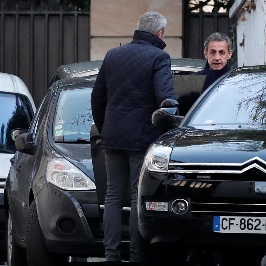 Quizzed: Nicolas Sarkozy leaves home in Paris yesterday on way to police PIC: REUTERS