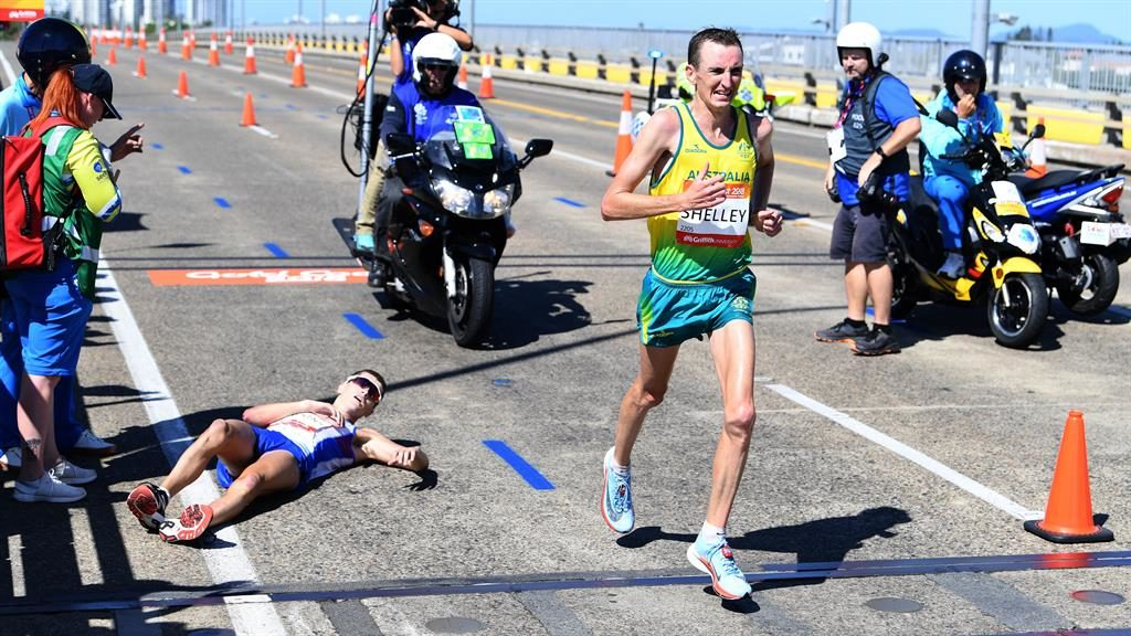 Overtaken: Callum Hawkins lies in the road as he is passed by Michael Shelley PICTURES: EPA/GETTY