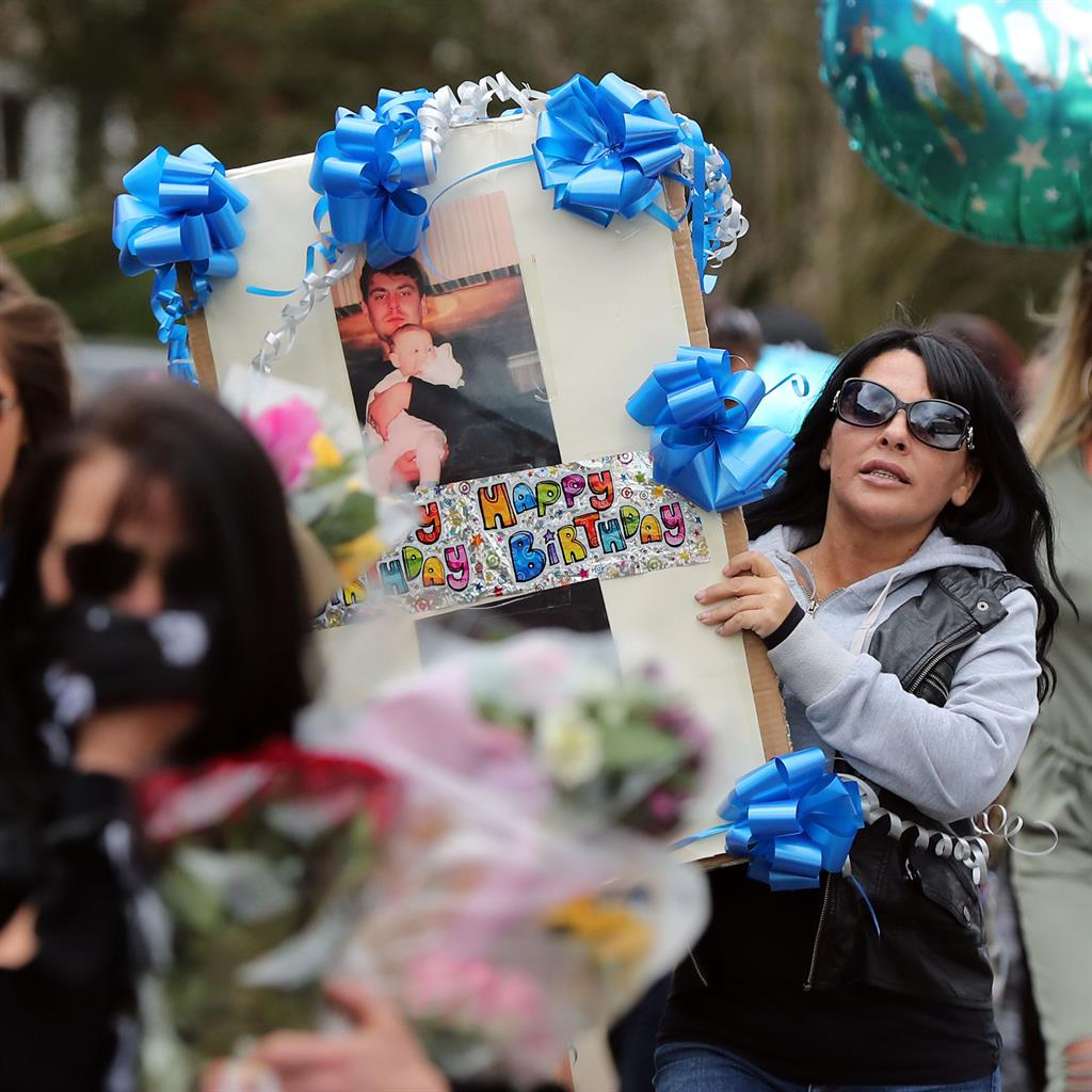 Tributes: A woman carries a placard with Vincent's picture PICS: PA