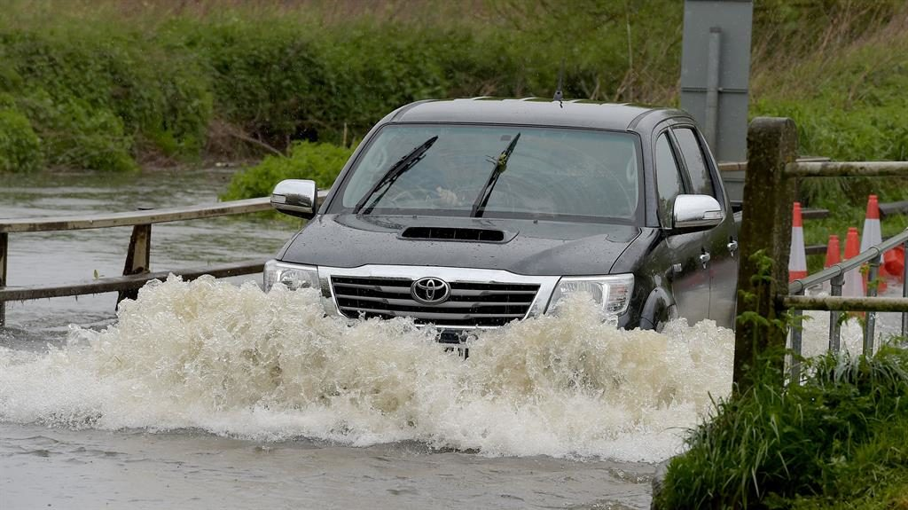 Car wash: A motorist gets in high water in Billericay, Essex PICTURE: REX