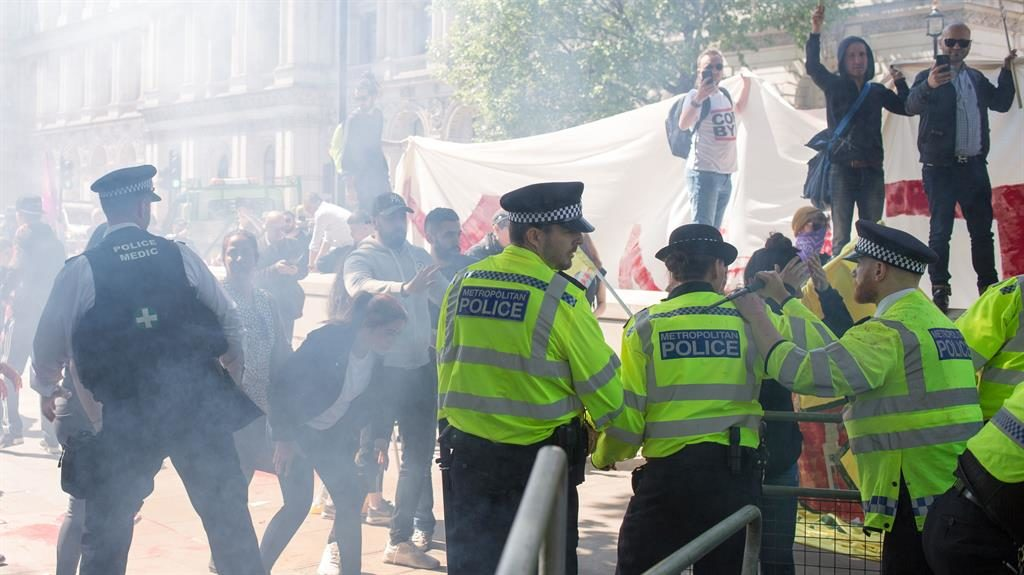 Chants: Police keep back the protesters, just yards from Downing Street PIC: REX