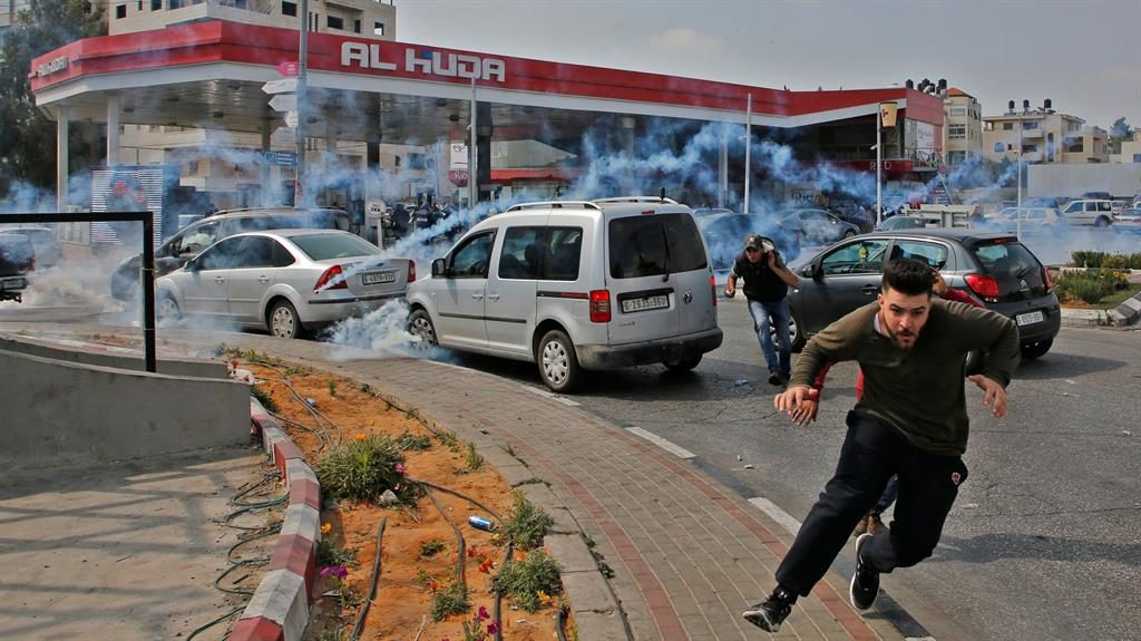 Taking cover: Palestinians run from tear gas shot at them during a protest in the West Bank city of Ramallah PICS: GETTY