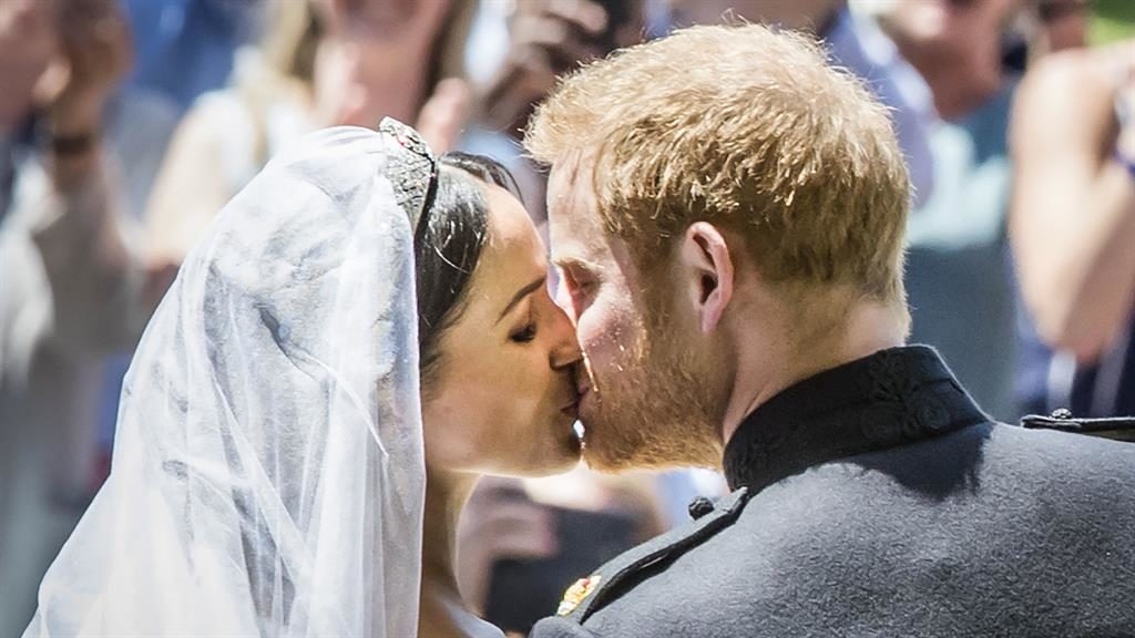 Kiss: Meghan and Harry show the world their love on the chapel steps PIC: AP