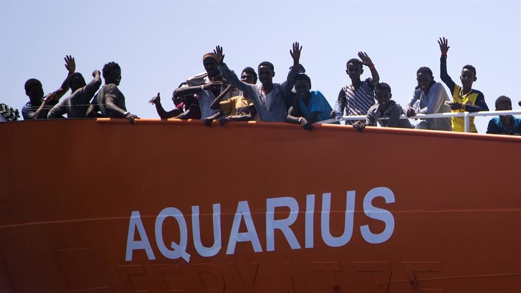 On the move: Migrants wave from Aquarius, which is on its way to Valencia PIC: AP