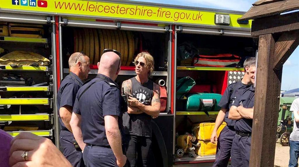Road crew: Guns N' Roses star Duff McKagan chats to firefighters at the miniature railway PIC: SWNS