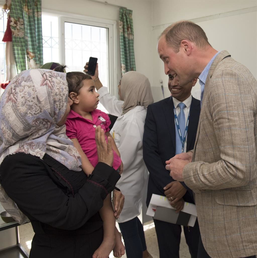 Doting dad: William chats with mothers of young children at a clinic in the camp PIC: PA