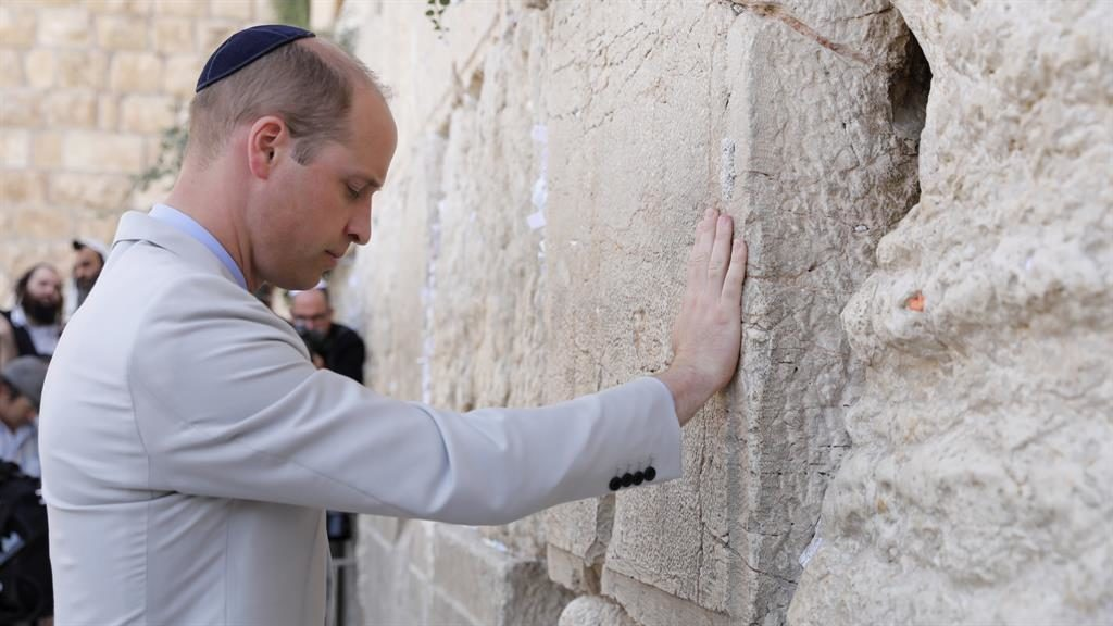 Holy site: William, wearing a kippah, touches the Western Wall in Jerusalem PICTURE: ABIR SULTAN/EPA