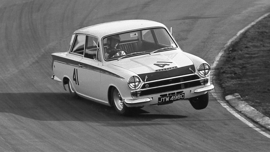 Motoring marvel: Clark (below) races the Cortina in 1965 PICTURES: BONHAMS/BNPS/GETTY