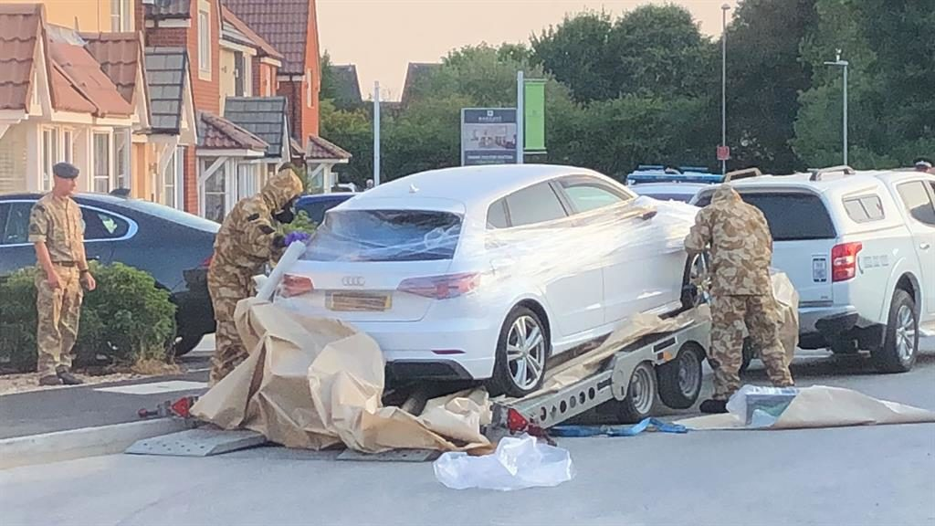 Toxic alert: Car is wrapped in plastic by a team wearing gas masks PICTURE:SWNS