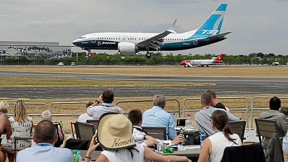 Landing deals: Spectators watch a Boeing 737 land at the Farnborough Airshow in Hampshire PIC: AP