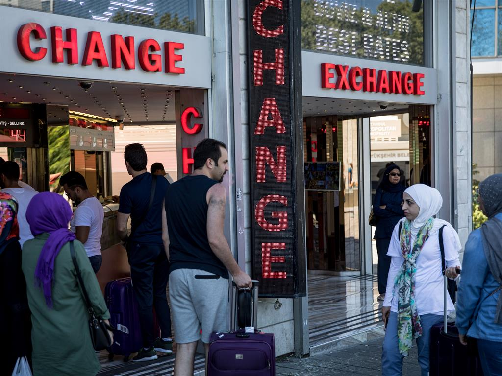 Cash flow Turks change money at an exchange in Istanbul. The Turkish lira recovered slightly after previous days' heavy losses