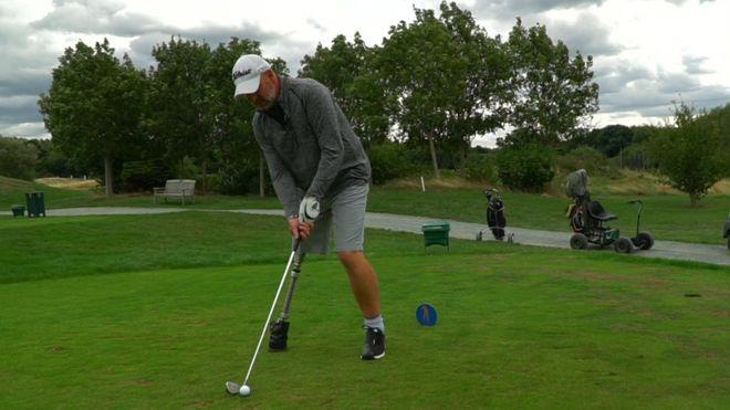 Buggybear: Paul Houghton tees up shot. (Below) the golf cart he's been told he can't use on course