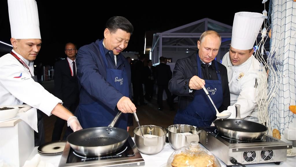 Going into batter: Presidents Xi (left) and Putin try their hands at pancake making at a street food exhibition PIC: GETTY