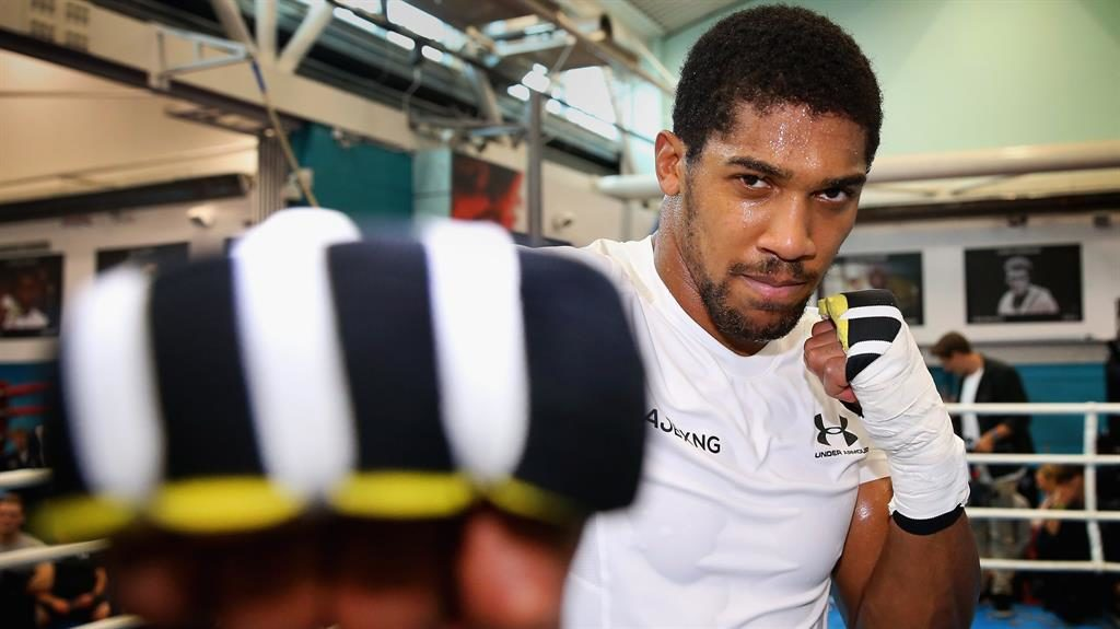 Cross fire: Joshua trains in Sheffield yesterday as he prepares to defend his world titles PICTURE: GETTY