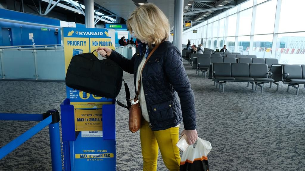 Does it fit: A Ryanair passenger measures space for a 'personal bag' PICTURE: PIXEL8000