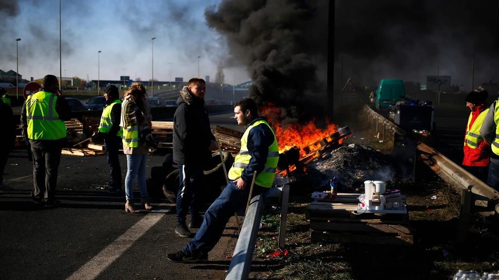 Fired up: 'Yellow vest' protesters use burning pallets to block a road in Caen, western France PICTURE: AFP