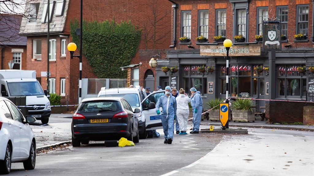 Inquiry: Police in forensics gear examine Haydons Road near the supermarket in Wimbledon PICTURE: EMPICS