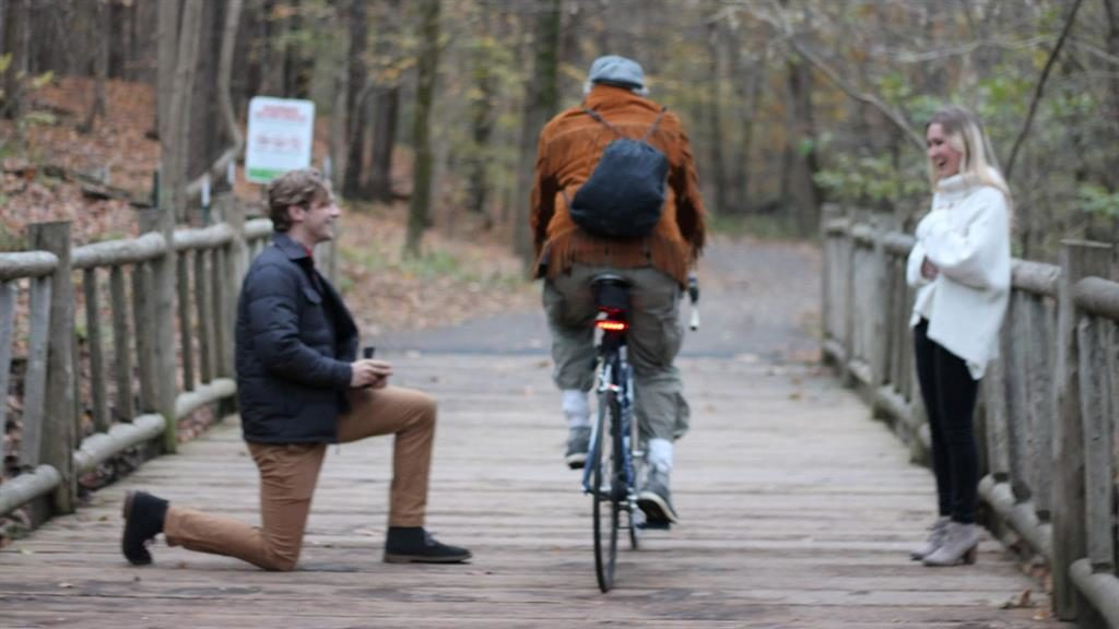 Will you... get out the way!: A cyclist whizzes by as Blake pops the question