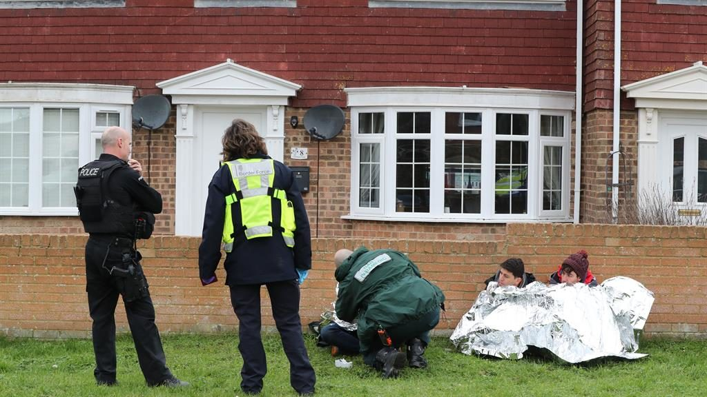 Cold comfort: A paramedic tends to one of the three suspected migrants found outside a house in Lydd PICTURE: PA