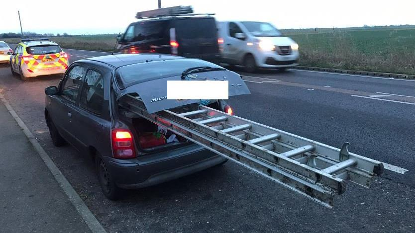 Height of stupidity: The 10-metre ladder was sticking out of a Nissan Micra
