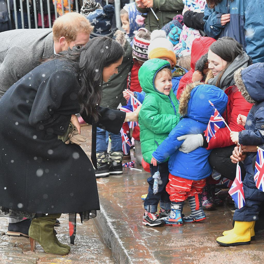 Royal visit: The Duke and Duchess meet nursery children who appear more interested in their biscuits PICTURES: PA