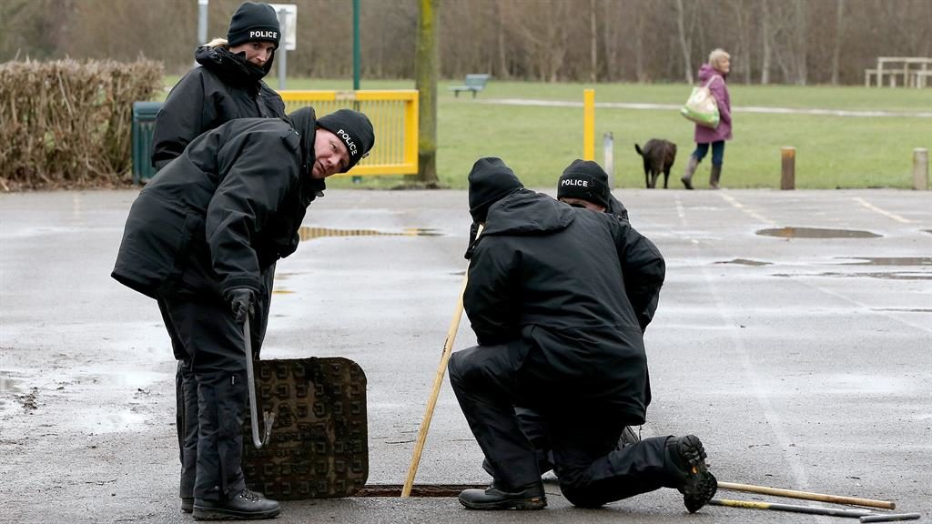Intensive search: Police check under a manhole cover PICTURE: PA