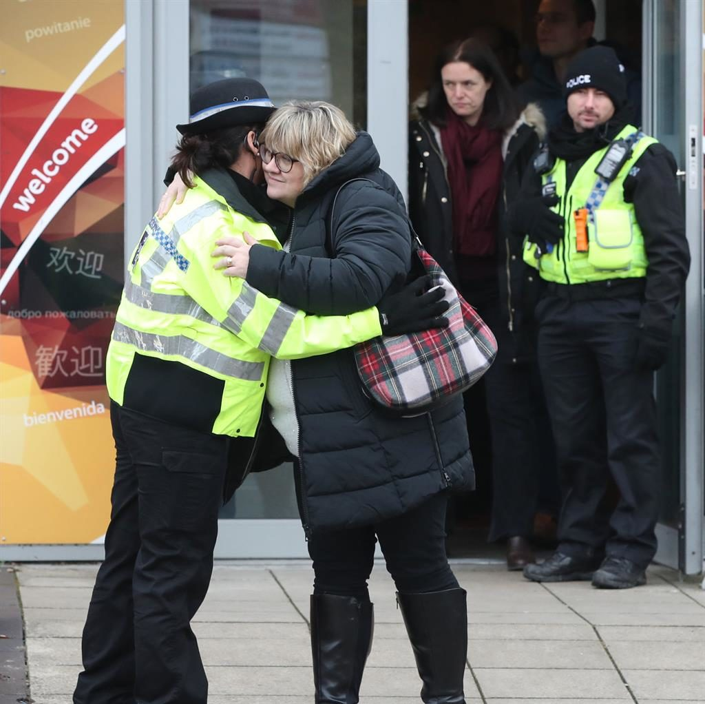 Shoulder to cry on: Lisa Squire hugs a police officer in Hull PICTURE: PA