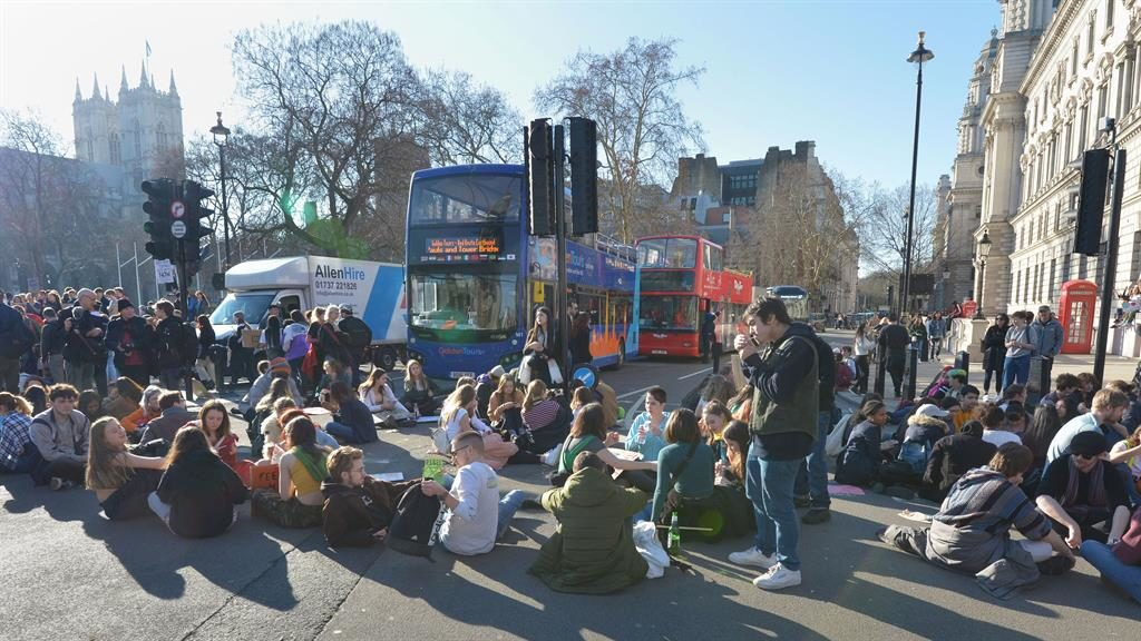 Break time: Young demonstrators sit in the road during the climate change protest in Parliament Square, Westminster, London PICTURES: PA