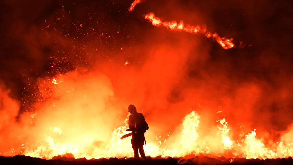 Hills are alight: A firefighter confronts huge moor inferno PICTURE: GETTY