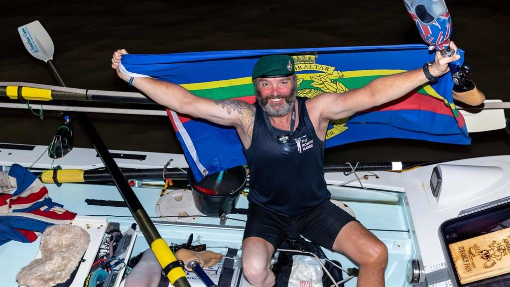 In the oar zone: Lee Spencer clutches his prosthesis as he raises flag of Marines