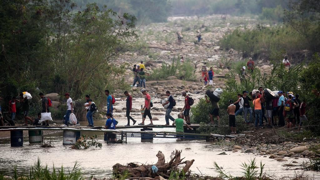Exodus: Migrants cross makeshift bridge at Colombian border PICTURE: GETTY