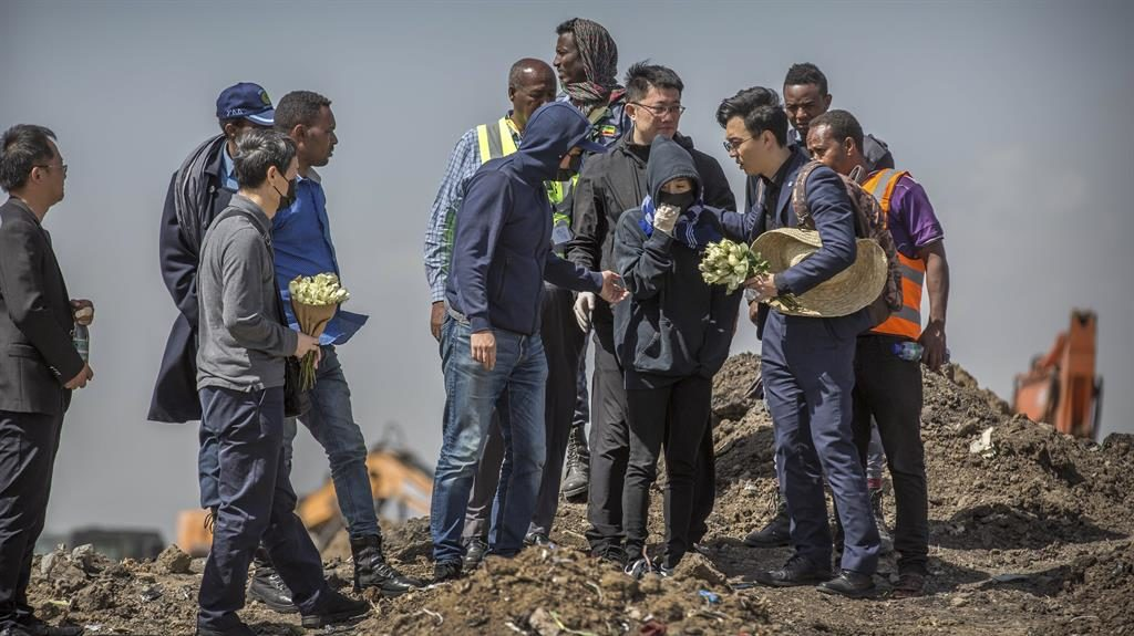 Mourning: Families bring flowers to the crash site in Ethiopia PICTURE: AP