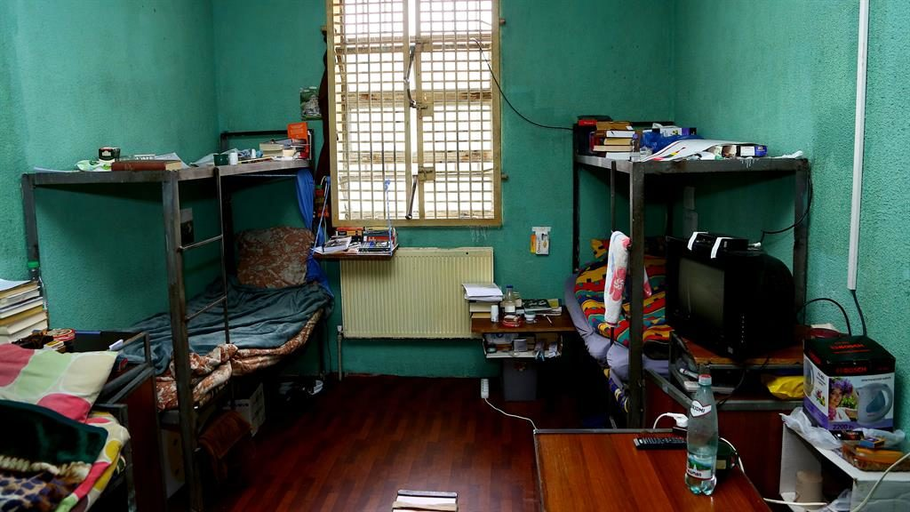 Room 101: Shepherd's cell is dingy but there are books and a TV and (below) heavily padlocked door PICTURE: DAILY MAIL