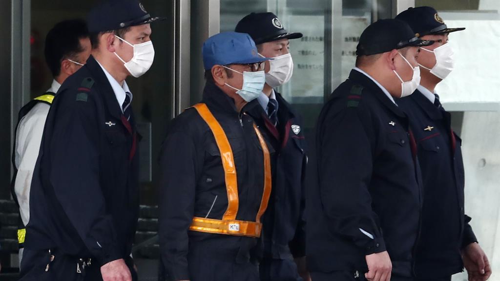 Undercover boss Ghosn in light blue cap emerges