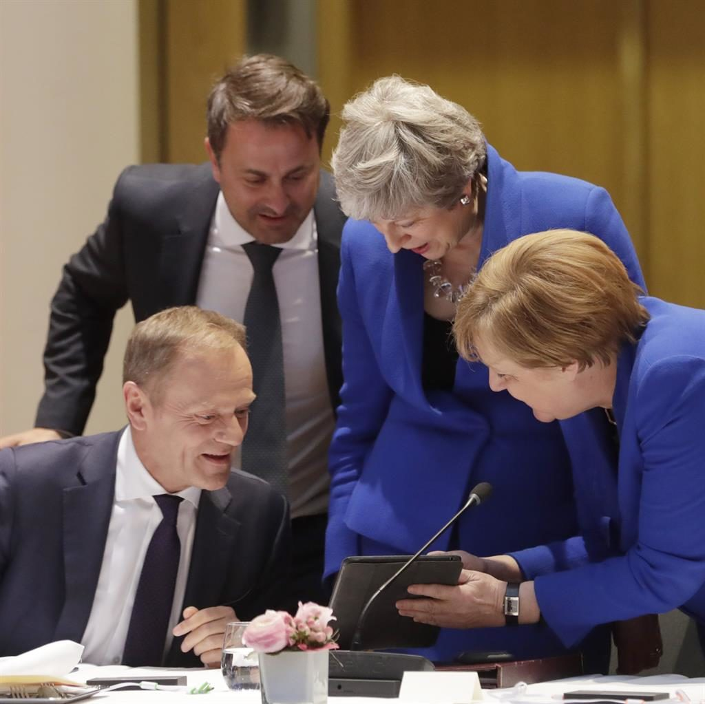 Bluesome twosome: Luxembourg PM Xavier Bettel (standing) and Donald Tusk look at images with Mrs May and Mrs Merkel PICTURE: EPA