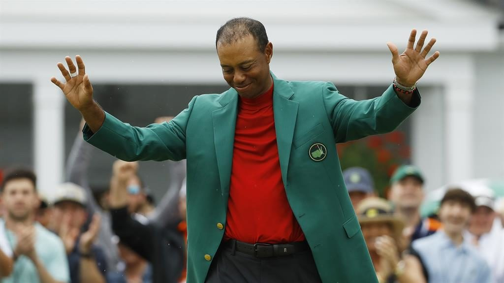 Suits you, Tiger: Woods with the green jacket after he won his fifth Masters title at Augusta yesterday
