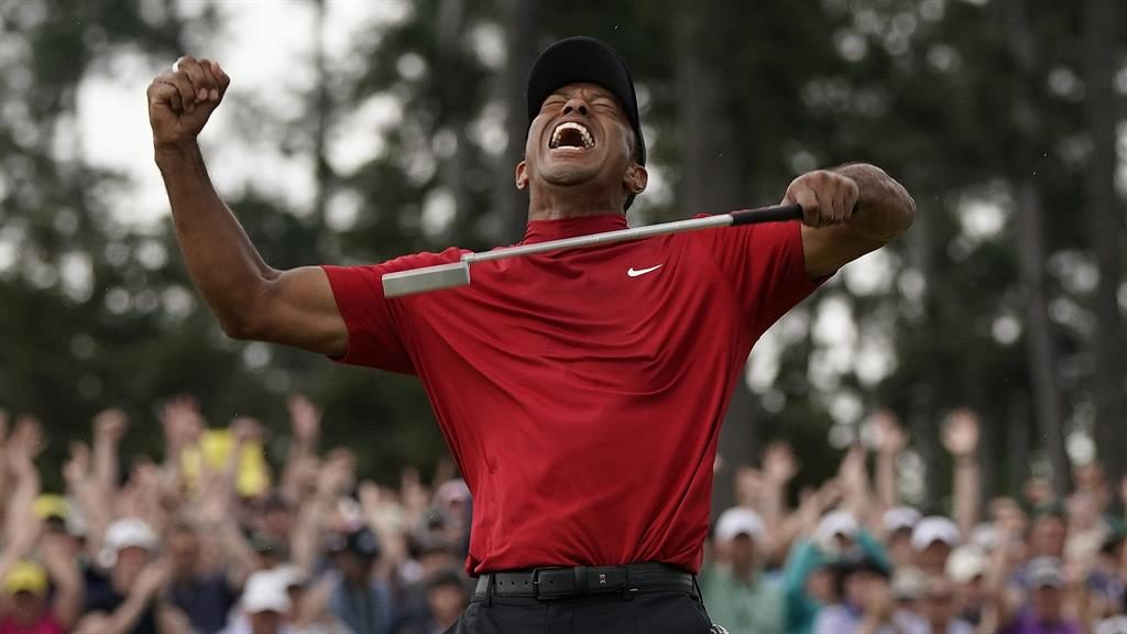 Tiger roar: Woods lets his emotions out after sinking the winning putt at Augusta yesterday