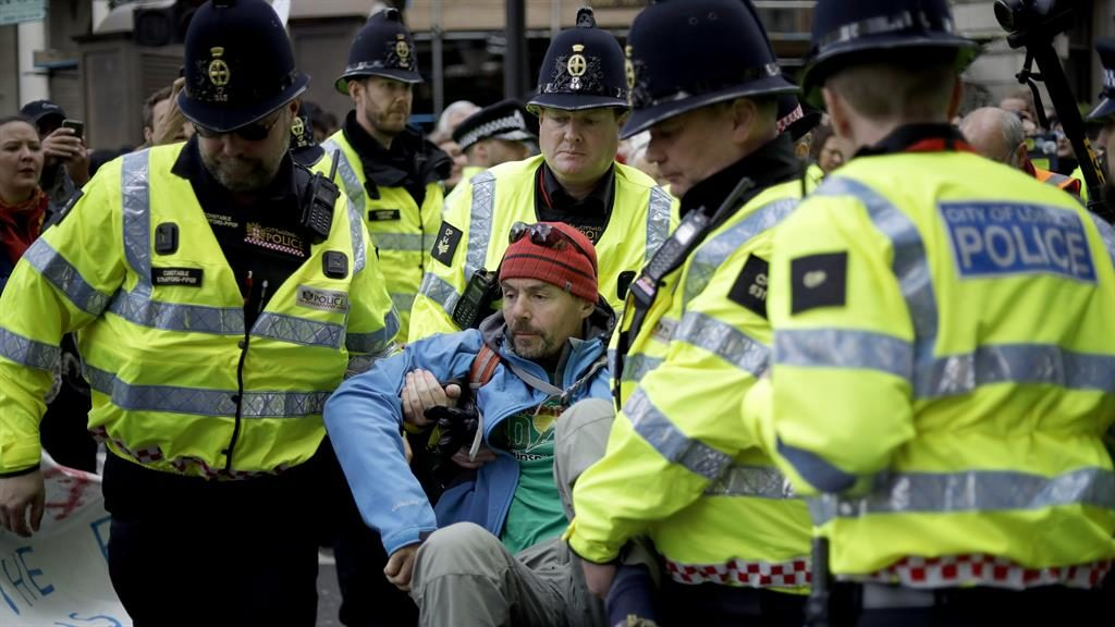 Protests: An activist blocking a London street is removed by police PICTURE: AP