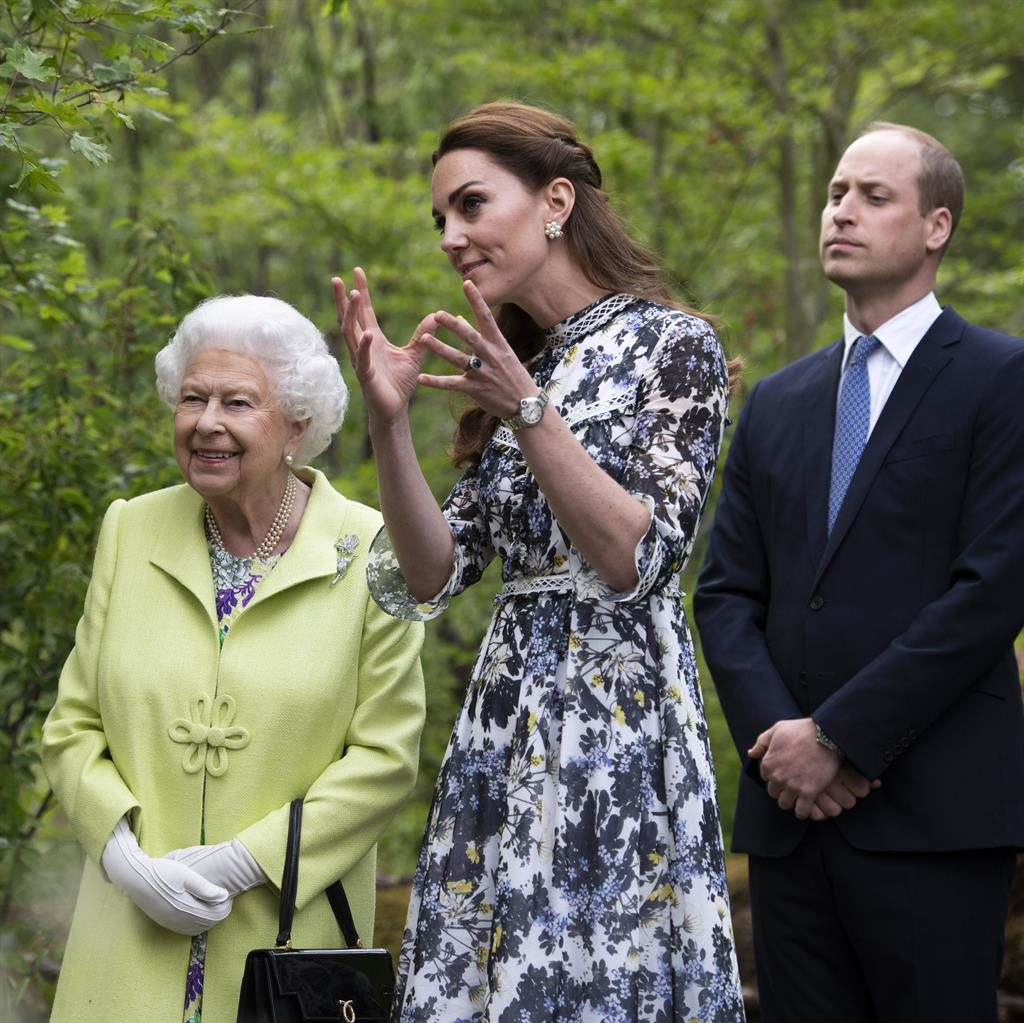 Green designs: The Queen, dressed in a floral dress and lime-coloured coat, listens as Kate talks about her exhibit