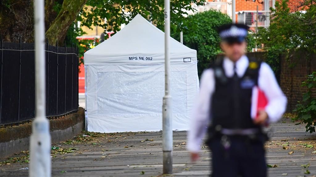 Murder enquiry: A police forensic tent where a man in his 40s was stabbed to death in Stratford. Below, officers at the scene
