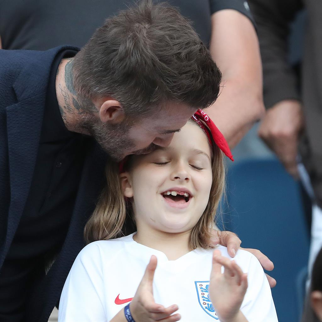 Becks' peck: A tender kiss for Harper last night and (below) meeting the England side PICTURES: GETTY/REX/INSTAGRAM