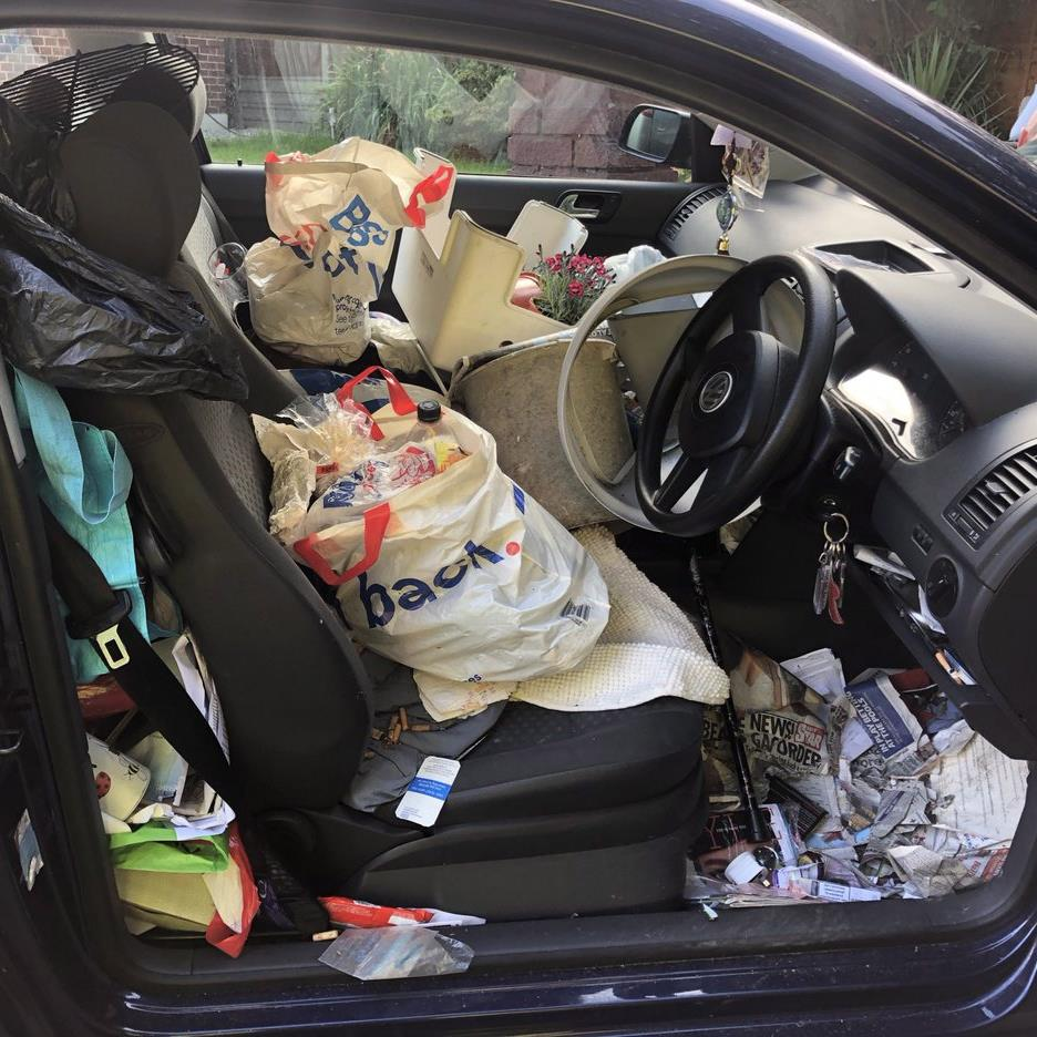 Vehicle crashes as owner can not find handbrake under mounts of rubbish
