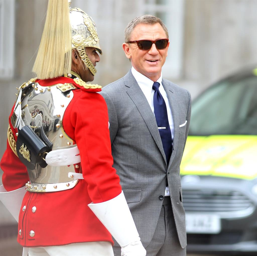 Horsing around: Daniel Craig jokes with a Household Cavalry officer during a break in filming yesterday PICTURES: MEGA/PA