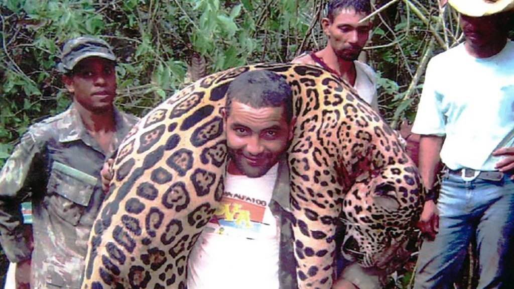 Sick trophy: A poacher carries a dead jaguar before the gang were rounded up by Brazilian police PICTURE: CEN